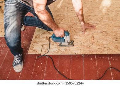 A carpenter works in a house with plywood and osb - inexpensive and quick decoration