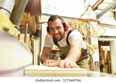 carpenter works in a joinery - workshop for woodworking and sawing