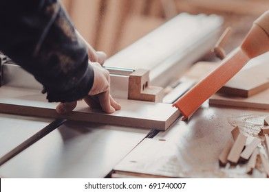 A carpenter works on woodworking the machine tool. Carpenter working on woodworking machines in carpentry shop. A man works in a carpentry shop. Saws furniture details with a circular saw