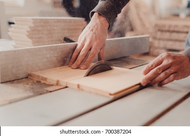 A carpenter works on woodworking the machine tool. Man collects furniture boxes. Saws furniture details with a circular saw. Process of sawing parts in parts