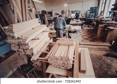 A carpenter works on woodworking the machine tool. Carpenter working on woodworking machines in carpentry shop. Man collects furniture boxes. view from the back