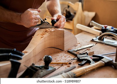 Carpenter works with a planer in a workshop for the production of vintage furniture. He makes cabriole leg for a table in the style of Louis and Queen Anne/Joiner Makes Cabriole Leg for Vintage Table