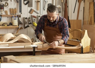 Carpenter works with a planer in a workshop for the production of vintage furniture. He makes cabriole leg for a table in the style of Louis XV, Queen Anne/Joiner Makes Cabriole Leg for Vintage Table