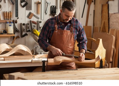 Carpenter works with a planer in a workshop for the production of vintage furniture. He makes cabriole leg for a table in the style of Queen Anne/Joiner Makes Cabriole Leg for Vintage Table