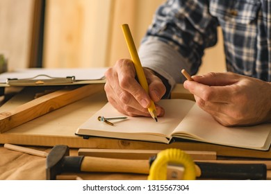 Carpenter writing project notes in small business woodwork workshop