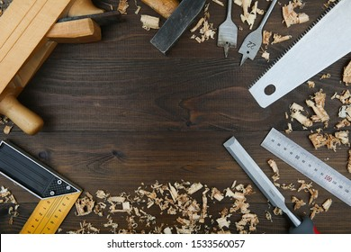 carpenter's background with copy space in the center. carpentry tools: planer, chisel, wood saw, square carpenter, ruler, wood drills with wood shavings on a wooden surface top view