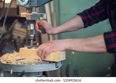 Carpenters with electric drill machine drilling wooden board at workshop. Profession, carpentry and woodwork concept.