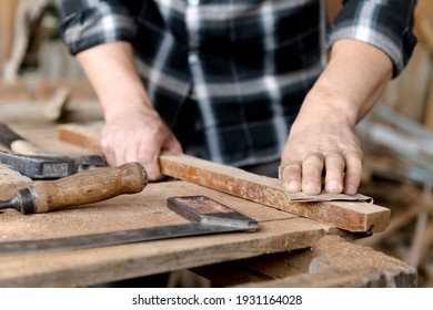 The carpenters experienced wood is using sandpaperSanding wood. Confident young handyman using sandpaper in workshop. Confident young handyman using sandpaper in furniture project.