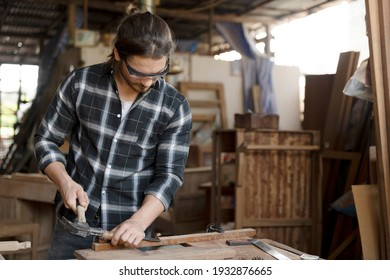 The carpenters experienced wood is using saw. Confident young handyman using ้hammer in workshop. Confident young handyman using hammer in furniture project.