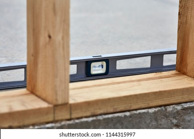 Carpenter's level laying on a cement slab next to 2x4 wood studs on a new construction site