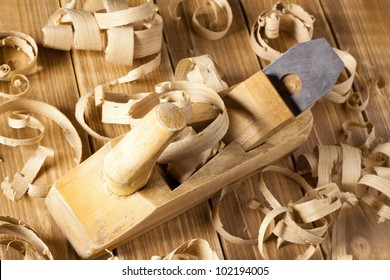 Carpenter's plane and shaving on a wooden planks