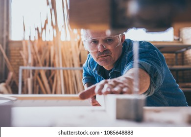 Carpenters using circular saw in workshop