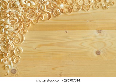 Carpentry motif.  Wooden background with decorative corner of curly shavings.