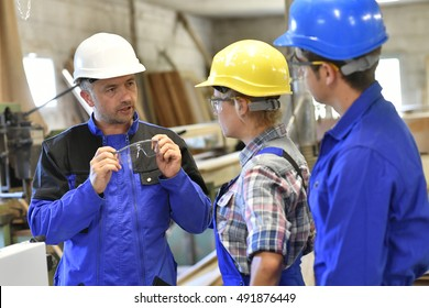 Carpentry teacher giving security instructions in workshop