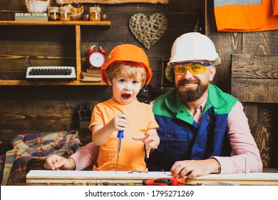 Carpentry woodwork and people concept - father and son with screwdriver screwdrivering screw into wood plank at workshop