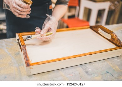 Carpentry workshop - master applies varnish and tints wooden craft serving tray