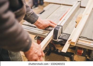 Carpentry workshop - master saws a wooden bar along
