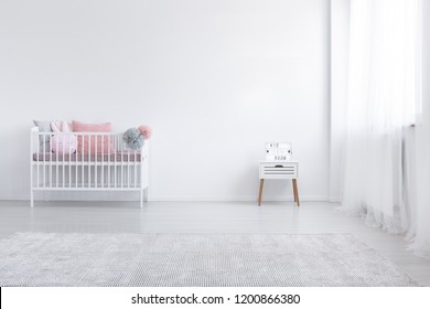 Carpet and cabinet in minimal white kid's bedroom interior with pink cushion in cradle. Real photo