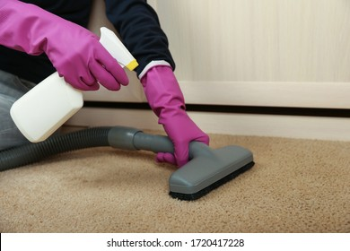 carpet cleaning concept. cleaner's hand in gloves sprays cleaning agent on the carpet and vacuums it. cleaning by vacuum cleaner