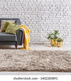 Carpet close up style, modern background sofa and gold object with pillow blanket, white brick wall.