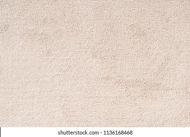Carpet floor mat or beach towel texture background in beige color made of wool or synthetic fibers, polypropylene, nylon or polyester material