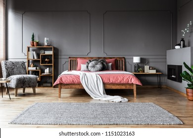 Carpet in spacious grey and pink bedroom interior with wooden bed and patterned armchair
