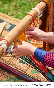 Carpet weaving. Woman hands weaving carpet on the loom. Weaving of handmade carpets closeup. Man's hands behind a loom.