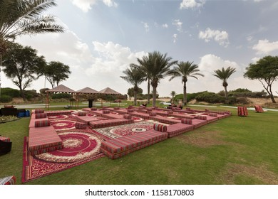 Carpets and cushions on a green lawn at an oasis in the desert