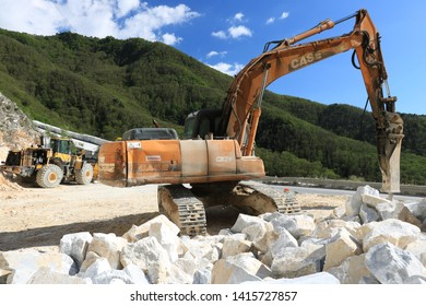 Carrara, Italy. 05/31/2019. Excavator with demolition hammer in a Carrara marble quarry. A large excavator shovel in a quarry in the Apuan Alps mountains.