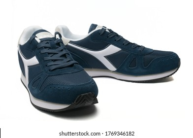 """Carrara, Italy - July 3, 2020 - A pair of Diadora """"Simple Run"""" blue shoe isolated on white background"""