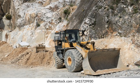 Carrara, Tuscany, Italy. 05/31/2019. Bulldozer in a Carrara marble quarry. A large Komatsu mechanical shovel in a quarry in the Apuan Alps mountains.