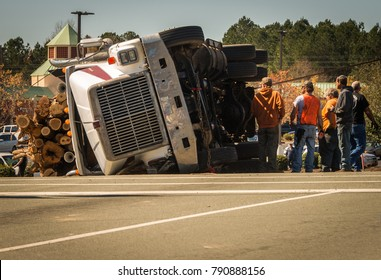 Carrboro, NC/US-March 10 2017:Overturned logging truck with workers on road