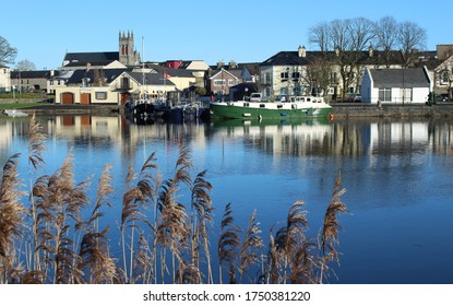 Carrick-on-Shannon, County Leitrim, Ireland viewed from across River Shannon against backdrop of blue sky on winter day