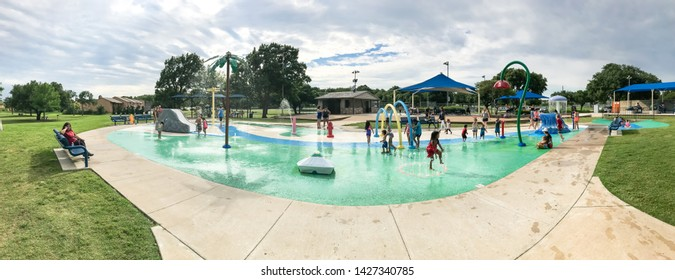 CARROLLTON, TX, US-JUNE 4, 2019: Panorama diverse kids enjoy water splash pad or spray ground at public park near Dallas. Water fountain activities for children and parent during summer time, overcast