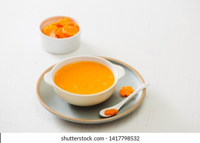 Carrot baby puree in bowl isolated on light background