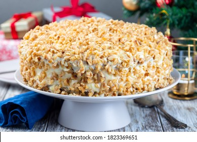 Carrot cake decorated with cream cheese frosting and walnuts, Christmas decoration on a background, horizontal