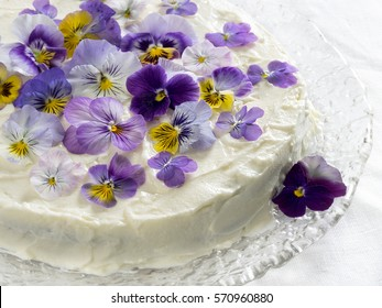 Carrot cake, decorated with edible flowers pansies