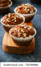 Carrot cake muffins with nuts, raisins and oats on a blue stone background.