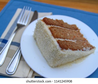 Carrot Cake slice with knife and fork and a blue place mat