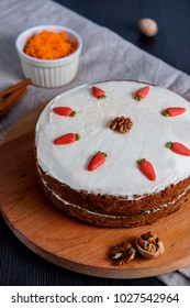 Carrot cake with sugar decoration on top, on wooden cutting board