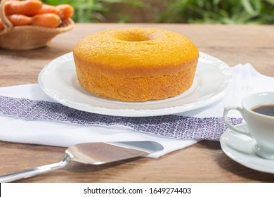 Carrot cake is a typical cake made in Brazilian houses. Cake on white plate and wooden table.