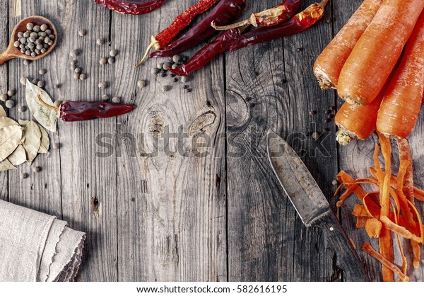 Carrot, chili and spices on gray wooden surface, top view, vintage toning