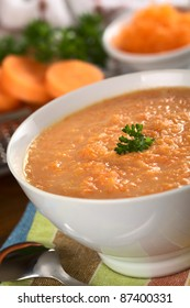 Carrot cream soup made of grated carrots and garnished with a parsley leaf (Selective Focus, Focus on the parsley leaf)