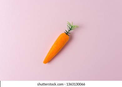 Carrot decoration on pastel pink background. Minimal spring composition.