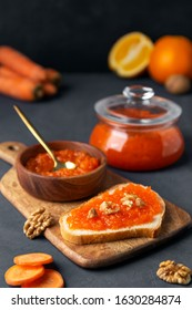 Carrot jam with bread and a jar on a dark background - Shutterstock ID 1630284874