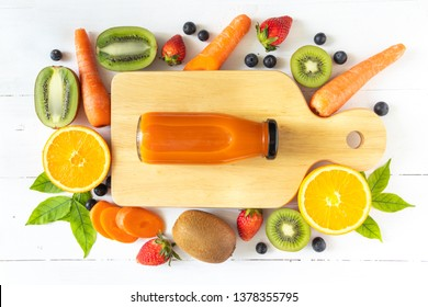 Carrot juice in a glass bottle on white wooden background, flay lay view of natural source of carotene