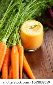Carrot juice in glass and fresh carrots Healthy food on wooden background