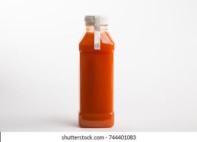 Carrot juice with in plastic bottle on the white background. Fresh detox juice diet. Organic. Big size bottle