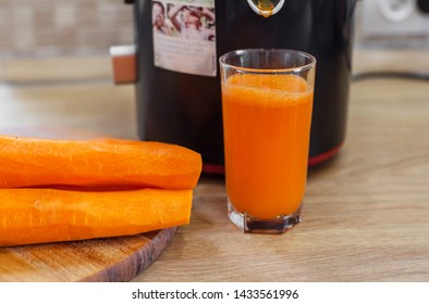 Carrot juice. Process preparation of fresh juice in juicer. Process of making juice in a juicer.