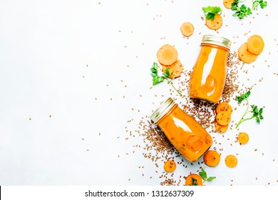Carrot juice or smoothies with flax seeds in glass bottles, vegan beverage, healthy drink for clean raw diet, selective focus